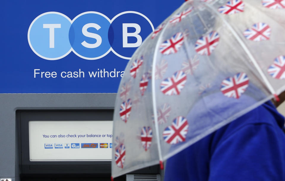 A pedestrian shelters from the rain beneath a British Union flag themed umbrella as they pass an automated teller machine (ATM) outside a TSB bank branch. Photo: Chris Ratcliffe/Bloomberg via Getty Images