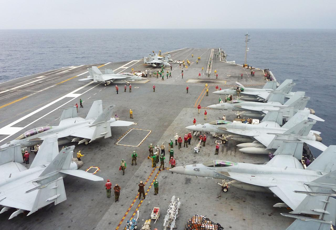 U.S. Navy FA-18 Hornets cram the flight deck of the USS George Washington during a joint military exercise with Japan in the Pacific Ocean near Japan's southernmost island of Okinawa Thursday, Nov. 28, 2013. The 13-day drill ended in the day as an air defense zone newly declared by China Saturday, Nov. 23 in the East China Sea has raised some tensions in the region. (AP Photo/Kyodo News) JAPAN OUT, MANDATORY CREDIT