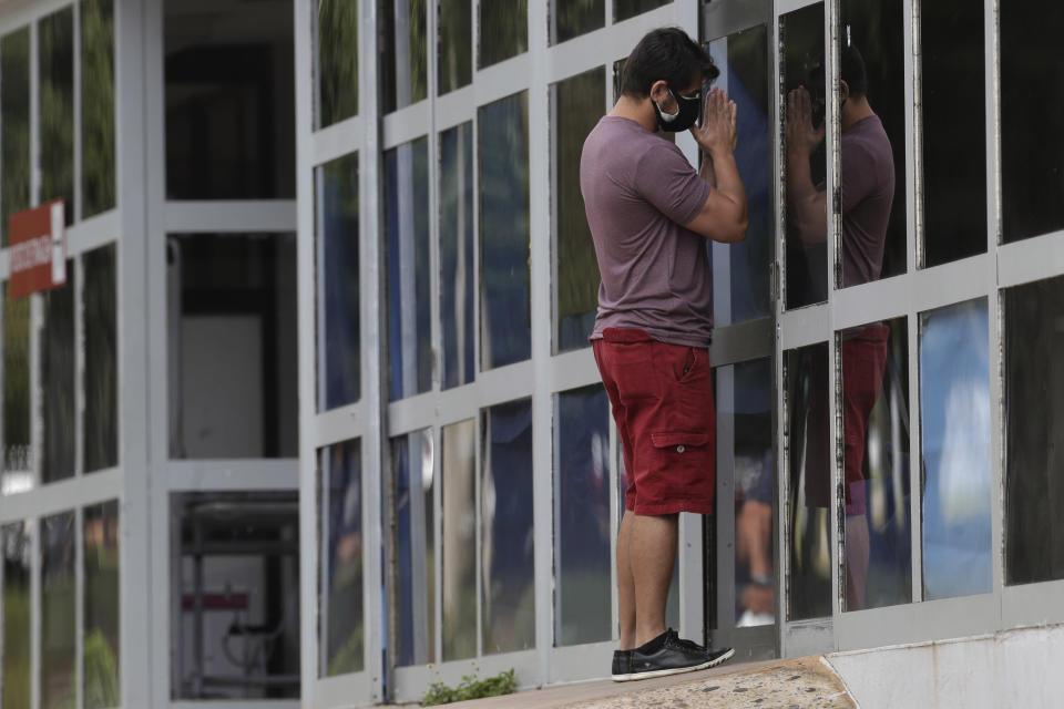 Marcio Moraes prays outside the window of an improvised ICU where his 25-year-old brother was hospitalized two days prior for COVID-19 at the public HRAN Hospital in Brasilia, Brazil, Monday, March 8, 2021. (AP Photo/Eraldo Peres)