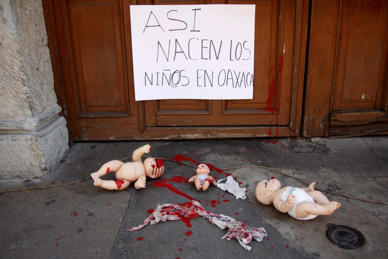"In this Tuesday, Feb. 18, 2014 photo, baby dolls representing children born in the streets are shown during a protest outside the Ministry of Health in Oaxaca , Mexico. The sign on the door reads in Spanish, ""The children in Oaxaca are born like this"". Women's rights advocates sought international help Thursday in trying to end what they call a pattern of poor indigenous Mexican women being turned away from hospitals while in labor, forcing them to give birth on lawns, patios or parking lots. (AP Photo/Luis Alberto Cruz)"