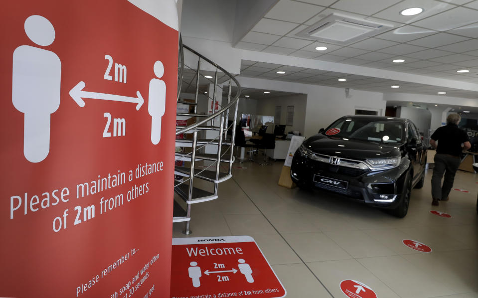 Social distancing signs at the Trident Honda car dealership, Ottershaw in Surrey, England, Friday, May 29, 2020. Lockdown restrictions are being lifted in England with car sales showrooms allowed to reopen from Monday. The Trident Honda showroom has strict social distancing measures in place with reduced cars on show to allow distancing and rigorous cleaning schedules arranged. (AP Photo/Kirsty Wigglesworth)