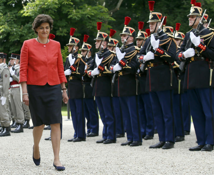 CORRECTS AGE TO 52 Newly named French defense minister, Sylvie Goulard, 52, reviews an honor guard during an handover ceremony with her predecessor, Jean-Yves Le Drian, in Paris, France, Wednesday, May 17, 2017. French President Emmanuel Macron named a mix of prominent and unknown figures from the left and the right Wednesday to make up the government tasked with pushing through his plans to reduce labor protections, tighten European unity and boost military spending. (AP Photo/Francois Mori)