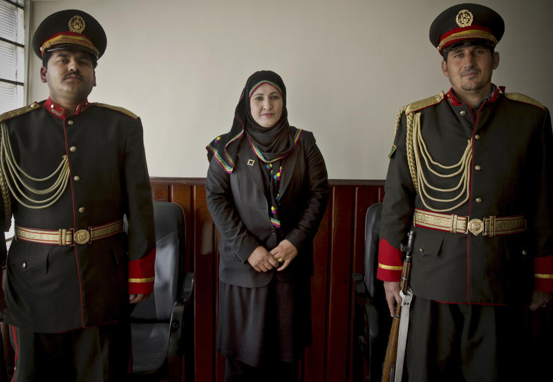 In this Wednesday, March 26, 2014 photo, Afghan lawmaker Toorpekai Patman from Kabul poses next to guards of honor in the parliament in Kabul, Afghanistan. In the last elections in 2010, 69 women won seats in Afghanistan's 249-seat parliament. The next parliamentary vote will be held in 2015, but first are the April 5 presidential and provincial council elections. (AP Photo/Anja Niedringhaus)