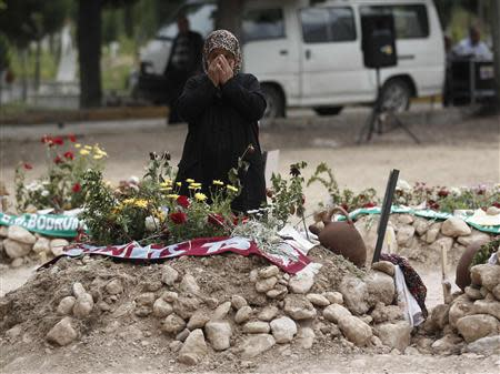 A woman mourns at the graves for miners who died in a fire at a coal mine, at a cemetery in Soma, a district in Turkey's western province of Manisa May 20, 2014. REUTERS/ Osman Orsal