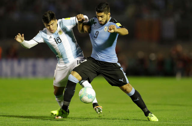 FILE - In this Thursday, Aug. 31, 2017 file photo, Uruguay's Luis Suarez, right, fights for the ball with Argentina's Marcos Acuaa during a 2018 World Cup qualifying soccer match in Montevideo, Uruguay. (AP Photo/Natacha Pisarenko, File)