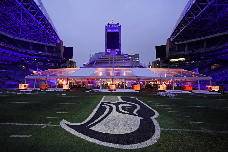 """People eat dinner in an outdoor dining tent set up near the logo of the Seattle Seahawks NFL football team on the 50-yard line at Lumen Field, Thursday, Feb. 18, 2021, in Seattle. The """"Field To Table"""" event was the first night of several weeks of dates that offer four-course meals cooked by local chefs and served on the field at tables socially distanced as a precaution against the COVID-19 pandemic, which has severely limited options for dining out at restaurants in the area. (AP Photo/Ted S. Warren)"""