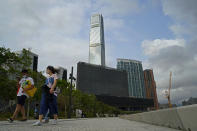 """People walk in front of """"M+"""" visual culture museum in the West Kowloon Cultural District of Hong Kong, Monday, March 29, 2021. The decision not to show a politically sensitive piece of art at an upcoming museum in Hong Kong as well as the Academy Awards this year not airing in the city for the first time in decades has prompted fears that Beijing's crackdown on dissent in Hong Kong has extended into the city's art and entertainment industry. (AP Photo/Kin Cheung)"""