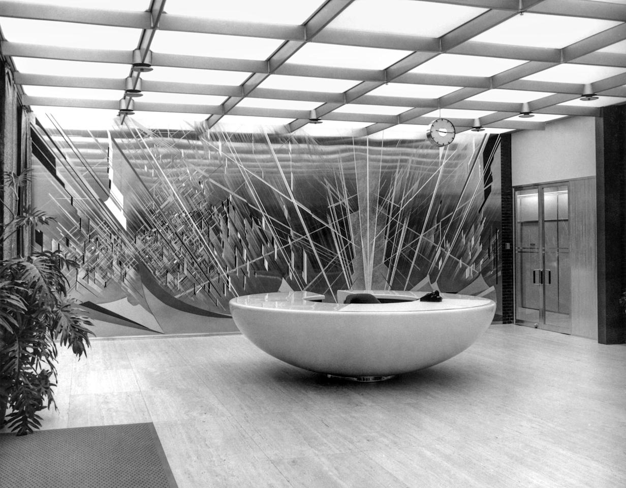 """Behind the """"teacup"""" desk in the lobby of the styling administration building is the artwork <em>Lines in Motion,</em> by Buell Mullen."""