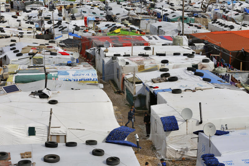 Syrian refugee stand outside their tents after heavy rain at a refugee camp, in the town of Bar Elias, in the Bekaa Valley, Lebanon, Jan. 10, 2019. (Photo: Bilal Hussein/AP)