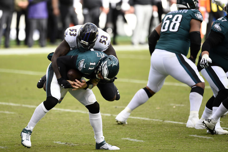Philadelphia Eagles' Carson Wentz (11) is tackled by Baltimore Ravens' Jihad Ward (53) during the second half of an NFL football game, Sunday, Oct. 18, 2020, in Philadelphia. (AP Photo/Derik Hamilton)
