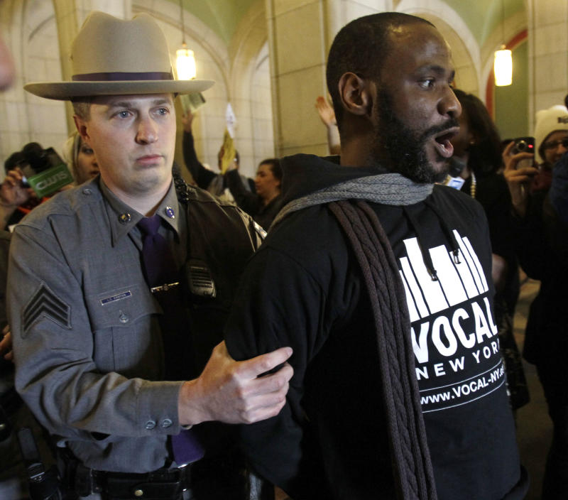 A protester is arrested by a New York State Police officer at the Capitol in Albany, N.Y., on Wednesday, March 2, 2011. More than 100 protesters blocked stairs and corridors protesting proposed cuts in Gov. Andrew Cuomo's budget, and several were arrested.  (AP Photo/Mike Groll)