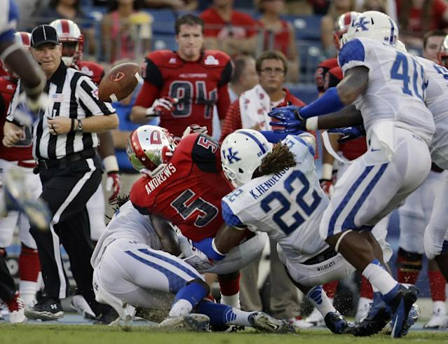 Western Kentucky running back Antonio Andrews (5) fumbles the ball as he is hit by Kentucky linebacker Khalid Henderson (22) in the first quarter of an NCAA college football game on Saturday, Aug. 31, 2013, in Nashville, Tenn. Kentucky linebacker Avery Williamson (40) recovered the ball on the play. (AP Photo/Mark Humphrey)