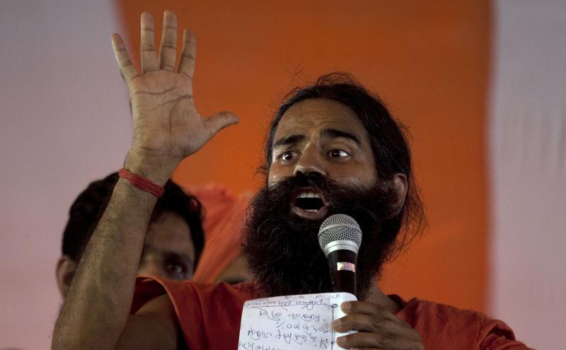 Renowned yoga guru Baba Ramdev addresses supporters, a day ahead of his proposed fast against corruption, in New Delhi, India, Friday, June 3, 2011. Ramdev said that he will go ahead with his plan of fasting from June 4, 2011 to protest against corruption and what he says is the Indian government's inaction in bringing back black money stashed abroad. (AP Photo/Manish Swarup)