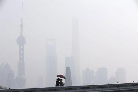 Women walk on a bridge in front of the financial district of Pudong amid heavy smog in Shanghai, China, December 15, 2015. REUTERS/Aly Song