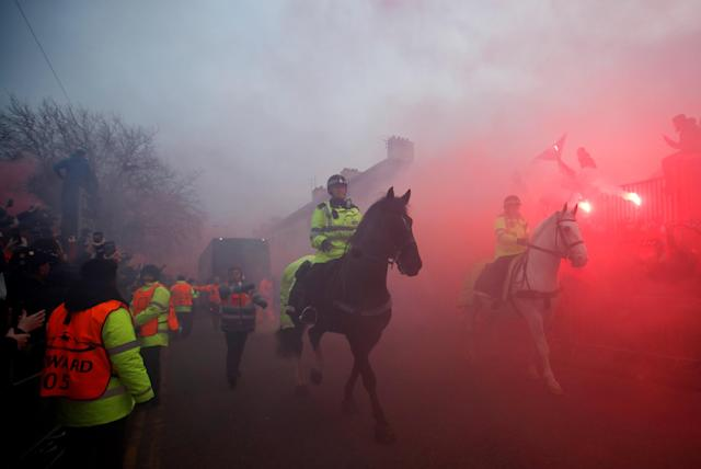 <p>Soccer Football – Champions League Quarter Final First Leg – Liverpool vs Manchester City – Anfield, Liverpool, Britain – April 4, 2018 Police officers clear the road as Liverpool fans set off flares as the Manchester City team bus approaches the stadium before the match Action Images via Reuters/Carl Recine </p>