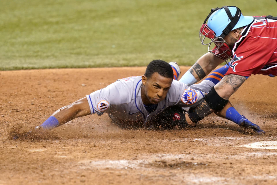 New York Mets' Johneshwy Fargas, left, is tagged out at the plate by Miami Marlins catcher Sandy Leon during the 12th inning of a baseball game Friday, May 21, 2021, in Miami. The Mets won 6-5 in 12 innings. (AP Photo/Lynne Sladky)