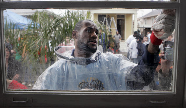 FILE - In this Feb. 15, 2008 file photo, NBA basketball player LeBron James scrapes paint from a window in the Lower 9th Ward of New Orleans. This week marks six years since NBA All-Stars ventured into New Orleans neighborhoods devastated by Hurricane Katrina to lend a hand with rebuilding. (AP Photo/Bill Haber, File)