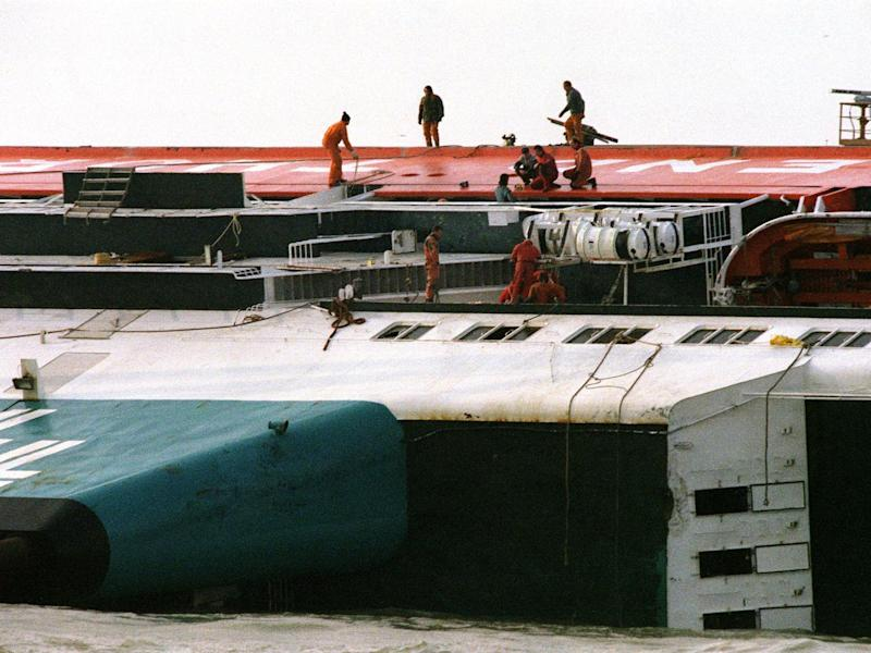 Rescuers on the hull of the ferry, which capsized in just two minutes (Getty)