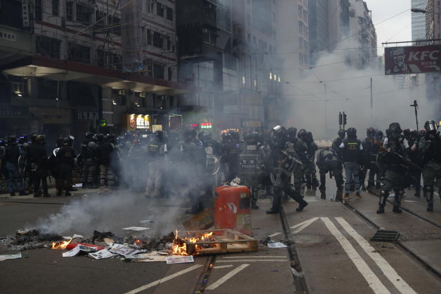 """Police arrive as protestors burn garbage to block traffic in Hong Kong, Sunday, Oct. 6, 2019. Shouting """"Wearing mask is not a crime,"""" tens of thousands of protesters braved the rain Sunday to march in central Hong Kong as a court rejected a second legal attempt to block a mask ban aimed at quashing violence during four months of pro-democracy rallies. (AP Photo/Vincent Thian)"""