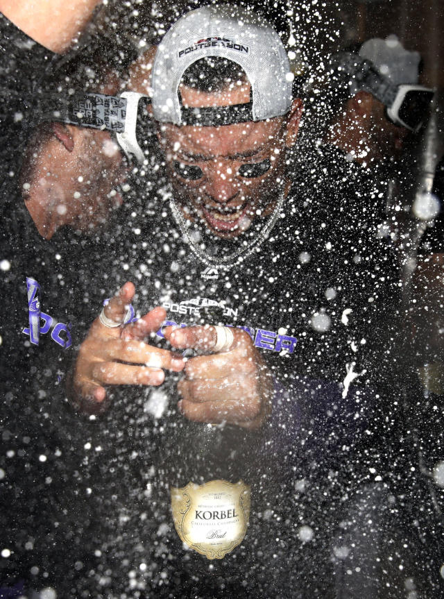Colorado Rockies' Carlos Gonzalez celebrates with teammates in the club house after defeating the Chicago Cubs 2-1 in the National League wild-card playoff baseball game early Wednesday, Oct. 3, 2018, in Chicago. (AP Photo/Nam Y. Huh)