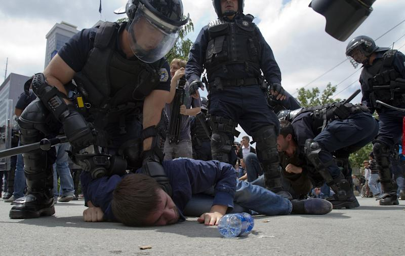 Kosovo police in riot gear detain a hardline opposition supporter protesting a deal with Serbia in capital Pristina, Kosovo, Thursday, June 27, 2013. Kosovo lawmakers voted in favor of an agreement to normalize relations with Serbia.( AP Photo / Visar Kryeziu )