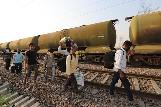 GHAZIABAD, UTTAR PRADESH, INDIA - 2020/05/13: Migrant workers with their belongings walk along a railway track returning to their home, during an extended nationwide lockdown to slow the spread of the coronavirus disease. (Photo by Amarjeet Kumar Singh/SOPA Images/LightRocket via Getty Images)