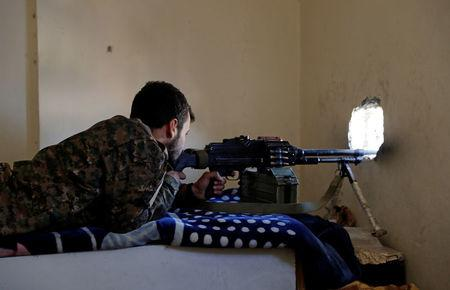 A fighter of Syrian Democratic Forces aims a machine gun towards the positions of the Islamic State militants holed up in the National Hotel complex at the frontline in Raqqa, Syria October 16, 2017.    REUTERS/Erik De Castro