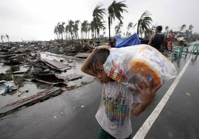 A boy carries relief goods, walking past the devastation caused by Typhoon Haiyan, in Tacloban city, Leyte province, central Philippines on Sunday, Nov. 10, 2013. Typhoon Haiyan, one of the most powerful storms on record, slammed into six central Philippine islands on Friday, leaving a wide swath of destruction and scores of people dead.(AP Photo/Aaron Favila)
