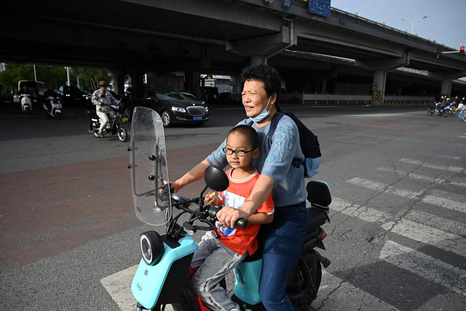 File: A woman carries a child on her electric bike in Beijing on 2 June, 2021 (AFP via Getty Images)