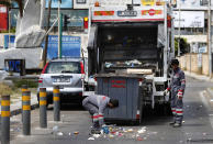 In this Saturday, May 23, 2020 photo, Bangladeshi and Syrian sanitation workers remove garbage from a street, in Beirut, Lebanon. Some 250,000 registered migrant laborers in Lebanon — maids, garbage collectors, farm hands and construction workers — are growing more desperate as a crippling economic and financial crisis sets in, coupled with coronavirus restrictions. With no functioning airports and exorbitant costs of repatriation flights, many are trapped, unable to go home. (AP Photo/Hussein Malla)