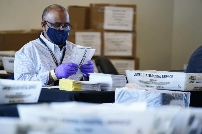 An election inspector looks at an absentee ballot as vote counting in the general election continues at State Farm Arena, Wednesday, Nov. 4, 2020, in Atlanta. (AP Photo/Brynn Anderson)