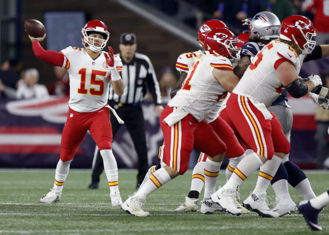 Kansas City Chiefs quarterback Patrick Mahomes, left, passes behind blocking linemen during the first half of an NFL football game against the New England Patriots, Sunday, Oct. 14, 2018, in Foxborough, Mass. (AP Photo/Michael Dwyer)