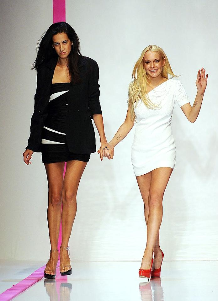 """Linds was all smiles while walking the runway at the Emmanuel Ungaro show during Paris Fashion Week in October 2009, which featured the first line designed by Estrella Archs under Lohan's """"artistic advisement."""" Unfortunately, Estrella's face in this photo said it all. The collection bombed and prompted even Emanuel Ungaro himself to say, """"Lindsay Lohan's collaboration was a disaster."""" Not surprisingly, she's no longer with the fashion house. Dominique Charriau/<a href=""""http://www.wireimage.com"""" target=""""new"""">WireImage.com</a> - October 4, 2009"""