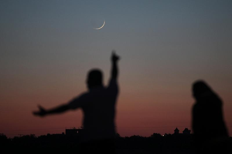 A Palestinian man points towards the crescent moon in Khan Yunis in the southern Gaza Strip on May 16, 2018, a day before the start of the Muslim holy month of Ramadan (AFP Photo/SAID KHATIB)