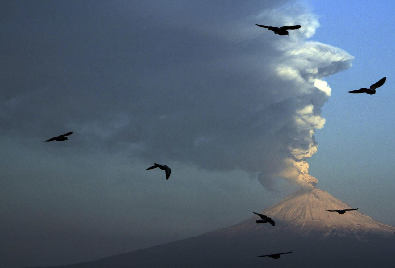 FILE - In this April 18, 2012 file photo, birds fly in the foreground as a plume of ash and steam rises from Popocatepetl volcano as seen from San Andres Cholula, Mexico, Wednesday, April 18, 2012. The volcano continues to shoot ash into the sky southeast of Mexico's capital, and television images on Friday, April 20, show a reddish glow near the crater. (AP Photo, File)