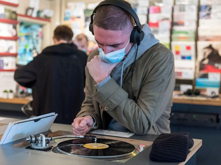 A customer wears a facemask while listening to a vinyl record in Soho, London (Rex Features)