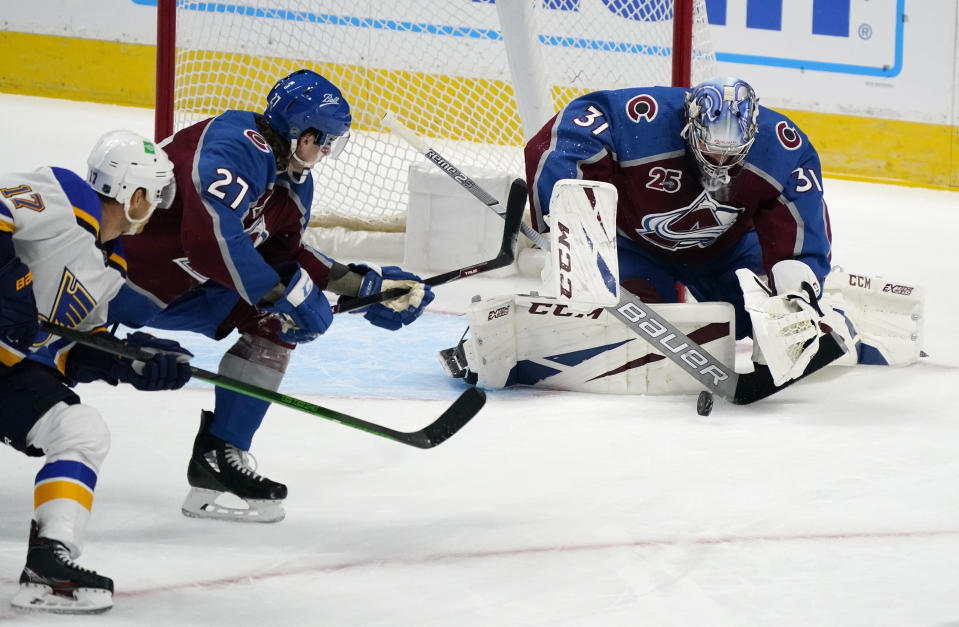 Colorado Avalanche goaltender Philipp Grubauer, right, stops a shot by St. Louis Blues left wing Jaden Schwartz, left, as Colorado defenseman Ryan Graves watches during the first period of an NHL hockey game Wednesday, Jan. 13, 2021, in Denver. (AP Photo/David Zalubowski)