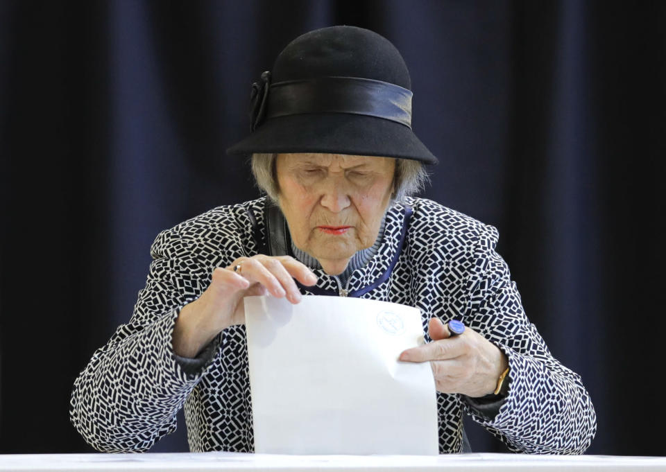 A woman casts her vote in Bucharest, Romania, Sunday, Nov. 10, 2019. Voting got underway in Romania's presidential election after a lackluster campaign overshadowed by a political crisis which saw a minority government installed just a few days ago. (AP Photo/Vadim Ghirda)