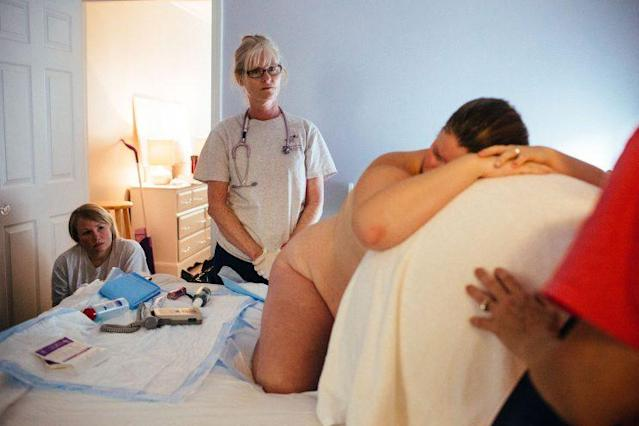 Ashley Loper struggled through the pain of a contraction while her midwife, Colleen Tullis, and midwifery student Star Croucher looked on. (Photo: Sara Naomi Lewkowicz for Yahoo News)