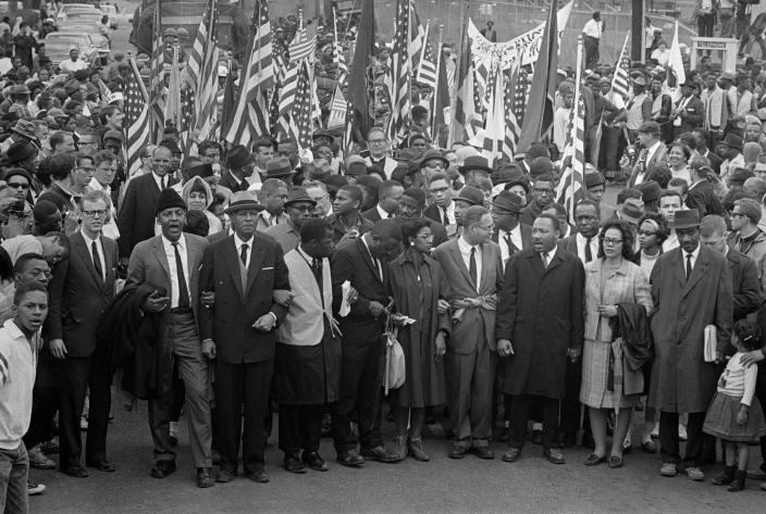 Dr. Martin Luther King (center) leads an estimated 10,00 or more civil rights marchers out on the last leg of their Selma-to-Montgomery march. Others identifiable in front row include: John Lewis, (2nd from left) of SNCC; King's aide, Reverend Ralph Abernathy (3rd from left); Dr. Ralph Bunche (5th from left, looking to side); Mrs. King (next to King); and Rev. Hosea Williams (carrying little girl, right). (Photo: Bettman Archive/Getty Images)