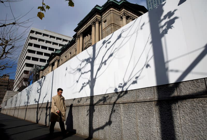 FILE PHOTO: Man walks past the Bank of Japan building in Tokyo