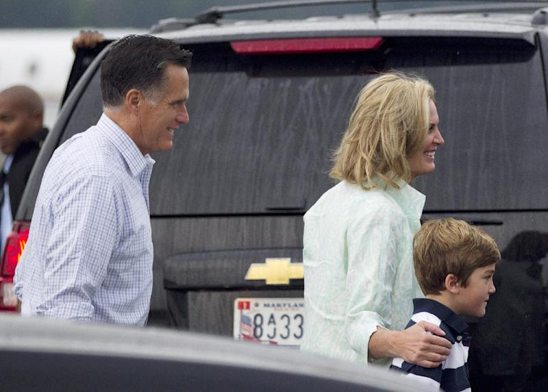 Republican presidential candidate, former Massachusetts Gov. Mitt Romney and his wife Ann, arrive to board their plane to Tampa with one of their grandchildren on Tuesday, Aug. 28, 2012 in Bedford, Mass.  (AP Photo/Evan Vucci)