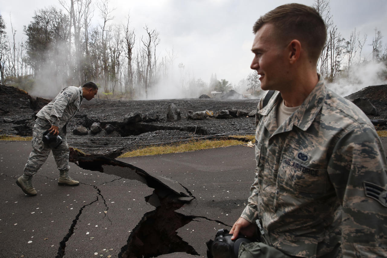U.S. Air National Guardsmen, Orlando Corpuz, left, and John Linzmeier survey cracks on the road in the Leilani Estates subdivision near Pahoa, Hawaii Friday, May 18, 2018. Hawaii residents covered their faces with masks after a volcano menacing the Big Island for weeks exploded, sending a mixture of pulverized rock, glass and crystal into the air in its strongest eruption of sandlike ash in days. (AP Photo/Jae C. Hong)