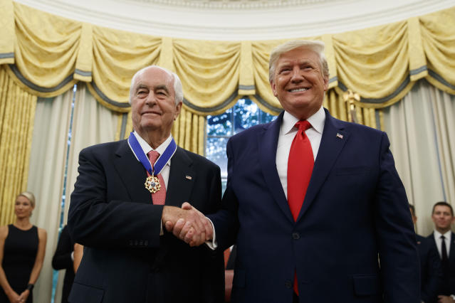 FILE - In this Oct. 24, 2019, file photo, President Donald Trump shakes hands with auto racing great Roger Penske during a Presidential Medal of Freedom ceremony in the Oval Office of the White House. Penske this week celebrated the crowning achievement of a career so rich in America's fabric that he last month received the Presidential Medal of Freedom by buying iconic Indianapolis Motor Speedway. On Sunday he will watch two of his drivers try to make NASCAR's championship race. (AP Photo/Alex Brandon, File)