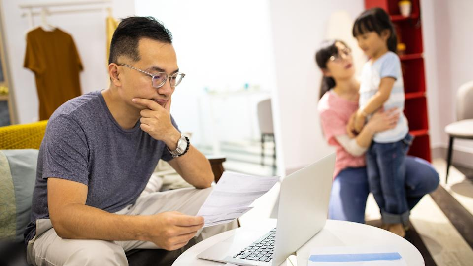 Worried man sitting on sofa in living room and holding paper, frustrated because of financial problems, wife and daughter playing near him.