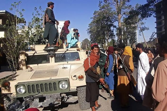 Taliban fighters stand on a vehicle along the roadside in Herat, Afghanistan's third biggest city