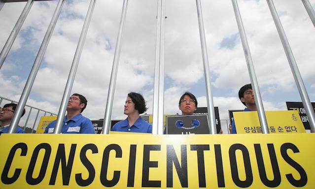 <p>Protesters hold placards behind mock prison bars in Seoul, South Korea, May 15, 2017, as they rally to demand the government not to punish conscientious objectors and introduce alternative service options for them in observance of the International Conscientious Objectors Day that fell on the same day. The rally was organized by Amnesty International Korea. (Photo: Yonhap South/EPA) </p>