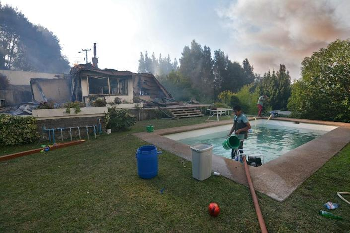 Men use water from a swimming pool to fight a wildfire in Concepcion, Chile on January 25, 2017 (AFP Photo/Guillermo SALGADO)