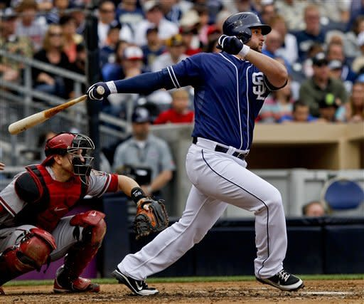 San Diego Padres' Yonder Alonso, right, drives a run producing base hit against the Arizona Diamondbacks during the fourth inning of a baseball game on Saturday, June 2, 2012, in San Diego. Diamondbacks catcher Miguel Montero, left, looks on. (AP Photo/Lenny Ignelzi)