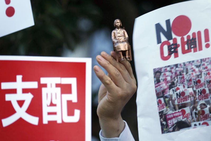 """In this Aug. 8, 2019 photo, one of protesters holds a miniature model of a statue of a girl symbolizing the issue of wartime """"comfort women"""" during a rally outside Japanese Prime Minister Shinzo Abe's residence in Tokyo. South Korea and Japan have locked themselves in a highly-public dispute over history and trade that in a span of weeks saw their relations sink to a low unseen in decades. (AP Photo/Eugene Hoshiko)"""
